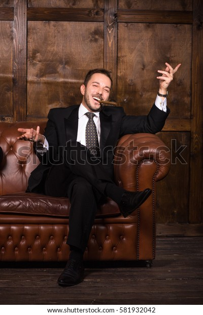 Business concept. Men's club concept. Happy man spending free time in restaurant. Luxury concept. Rich businessman with cigar sitting on sofa and looking at camera.