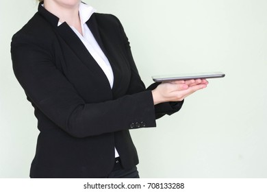 Business concept. new technologies. Tablet in hand. Business woman in a black jacket. Photo for your design.