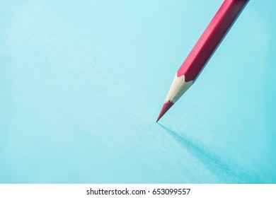 Business concept - one red color pencil stand on blue paper background. It's symbol of key point and confident.
