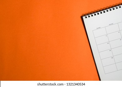 Business concept: orange background with calendar at the side and copy space