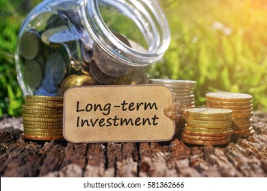 Business Concept - Paper tag written with LONG TERM INVESTMENT inscription. Coins stack, jar and nature background.