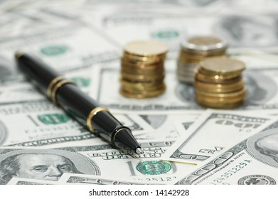 Business concept - pen, coins and american dollars