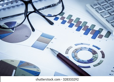 Business concept, Pen,eyeglasses and calculator on graph background,blue color tone