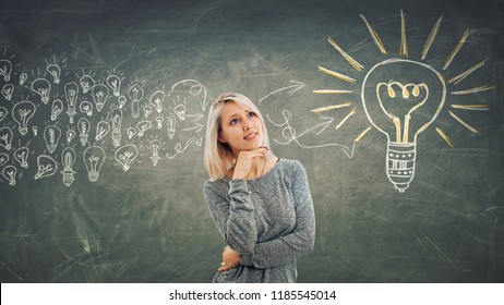 Business concept as a pensive girl with hand under chin, thinking gathering ideas into a big light bulb.