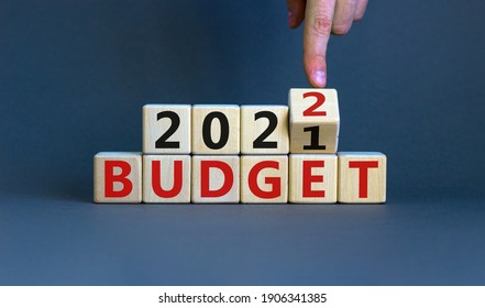 Business concept of planning 2022. Businessman flips a wooden cube and changes words 'BUDGET 2021' to 'BUDGET 2022'. Beautiful grey background, copy space.