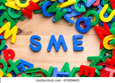 Business concept.  Plastic letters with text inside ,SME (or small and medium enterprises) on the table