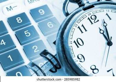 Business concept with pocket watch, calculator and documents
