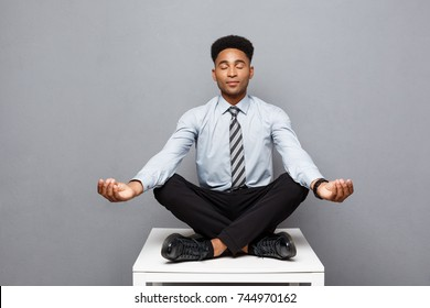 Business Concept - portrait of african american businessman doing meditation and yoga in before working.
