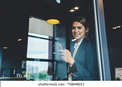 Business concept, portrait of smart casual dressed woman with mobile phone standing in open space office. Succesful meeting debreifing