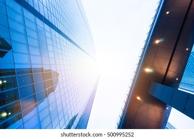 Business concept for real estate and corporate construction - looking up view in financial district, the silhouettes of skyscrapers city reflect blue sky, sun lights in Tokyo, Japan