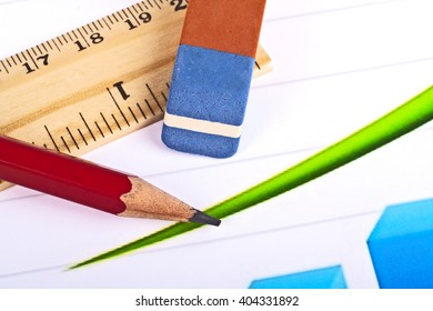 Business concept - red pencil, wooden ruler, eraser and graph