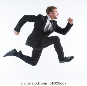 Business concept. Running young businessman excited, surprised and happy amazed isolated on white background.