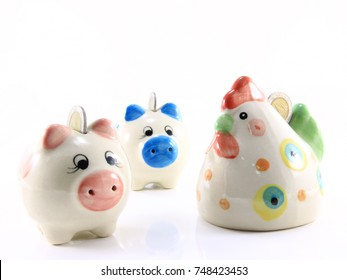 Business concept , save money , with coin , piggy and chicken bank ceramic model isolated on white background.Selection focus.