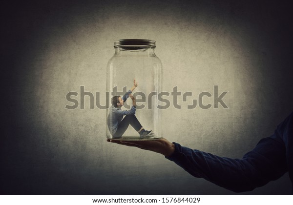 Business concept with a scared tiny man trapped inside a glass jar held by his gigantic boss hand. Surreal nightmare, helpless captive employee victim of abuse at work. Workplace bullying and conflict
