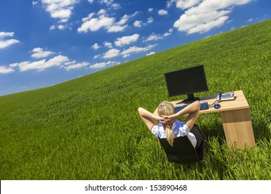 Business concept shot of a beautiful young woman or businesswoman relaxing at a desk with computer in a green field with a bright blue sky.