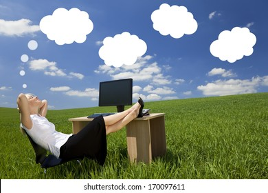 Business concept shot of a beautiful young woman relaxing at a desk in a green field day dreaming, white dream clouds in a blue sky.