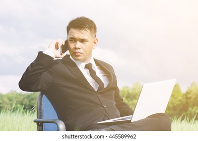 Business concept shot of a businessman sitting at a chair using a computer in a grass. Young businessman in sunny meadow nature office. Young man with smartphone.