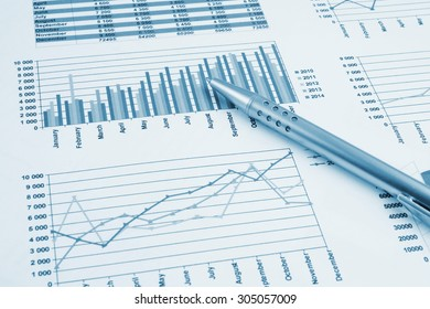 Business concept, silver pen on financial charts and graphs