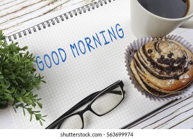 Business concept of simple breakfast, coffee and croissant with note pad,glasses and green plant. Copy space.
