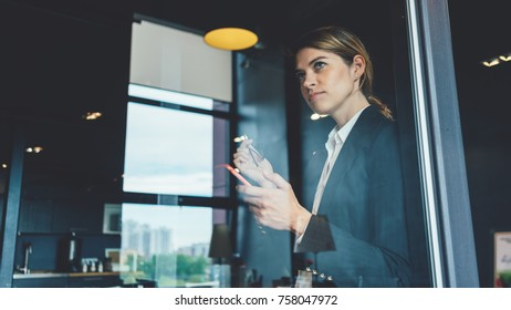 Business concept, smart casual dressed and thinking woman with mobile phone standing in open space office. Succesful meeting debreifing