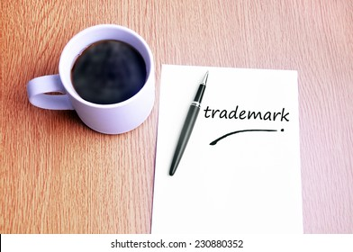 Business Concept - Steamy Coffee And Black Pen With White Paper Writing Trademark On The Table