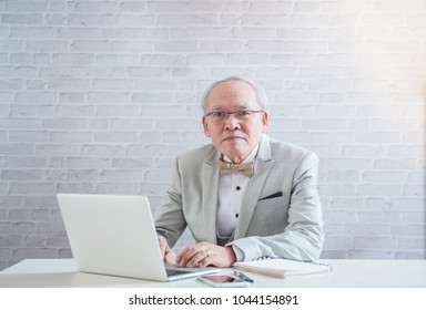 Business concept, in studio, Senior old man confident to work with the modern technology, laptop and smartphone at work place, he can adapt himself to use them run his business