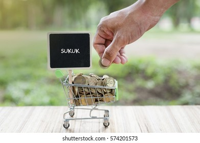 Business Concept : SUKUK word on black board with man hand holding coin putting on trolley over blur and sunlight background.