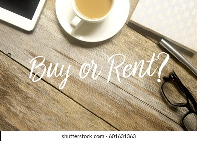A business concept. A tablet pc, cup of coffee, glasses, pen and notebook with BUY OR RENT written on wooden table.