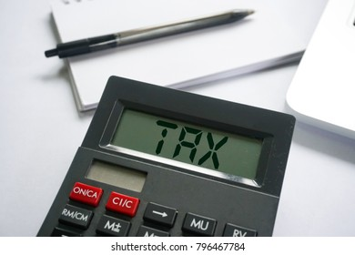 Business concept - TAX word on calculator on white desk
