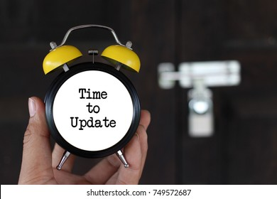 Business concept. time management. hand holding clock writing Time to update