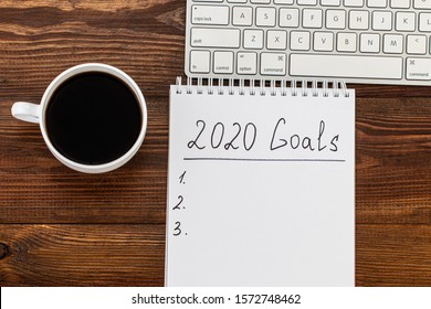 Business concept of top view 2020 goals list with notebook, cup of coffee over wooden desk.