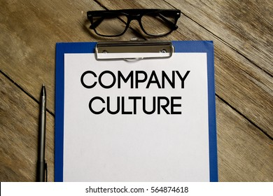A business Concept. Top view of clipboard and white sheet written with COMPANY CULTURE on wooden background.
