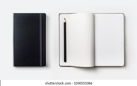 Business concept - Top view collection of black hardcover notebook, white open & flip curl rolled page and black pencil isolated on background for mockup