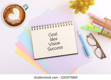 Business concept. top view notebook with pen, glasses and coffee cup writing Goal Idea Vision Success