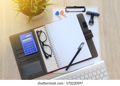 Business concept - Top view notebook empty with calculator, glasses, pen, rubber stamp and keyboard.copy space
