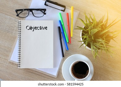 Business concept - Top view notebook writing Objective