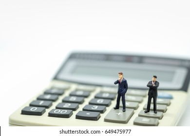 Business Concept. Two businessman miniature figures standing on calculator.
