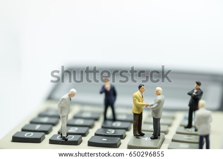 Business Concept. Two businessman miniature figures standing on calculator meeting with handshake and  another businessmen stand around the meeting.