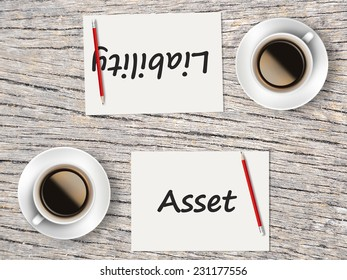 Business Concept : Two Coffee, Papers And Pencils On The Table  Facing Each Other Head To Head To Compare Between Asset And Liability.