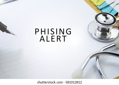 Business Concept, View of pen, stethoscope and clipper written with PHISING ALERT on blank paper background.