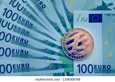 Business concept of virtual money; Business concept of virtual money; One coin golden Litecoin physical coin on a  of 100 euro banknot; toned.