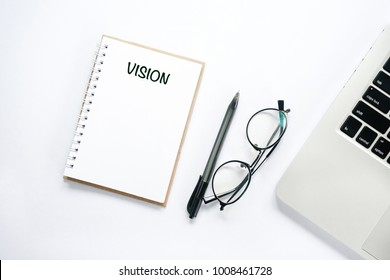 Business concept - VISION word written on notepad. Top view all objects