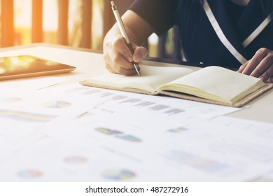 Business concept, Woman writing on the note and around her have many report papers