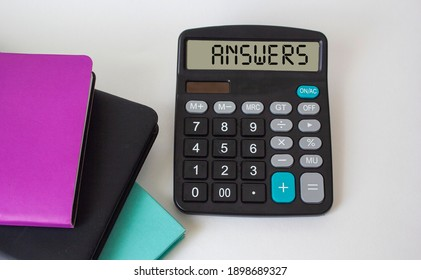 Business concept. The word Answers, written on the display of the calculator and on a white background, lie next to multi-colored notepads.