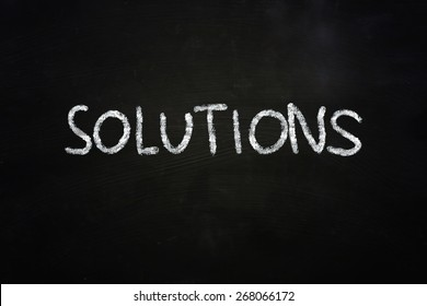 Business concept the word Solutions written with chalk on blackboard