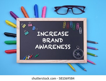 Business Concept writing INCREASE BRAND AWARENESS on Blackboard