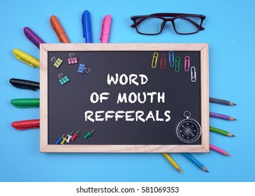 Business Concept writing WORD OF MOUTH REFFERALS on Blackboard