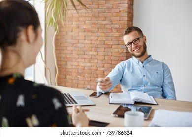 Business concept. Young dark-haired woman sitting in front of mature cheerful office manager on job interview, having relaxing talk about her experience and study degree