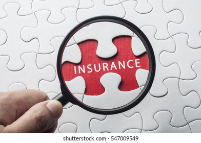 Business concept.Hand with magnifying glass searching for a piece of jigsaw puzzle with INSURANCE word.