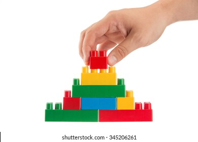 Business conception, man building a wall with plastic building blocks on white background
